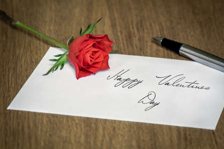 A love letter reading Happy Valentines Day with a rose and a pen on top. photo