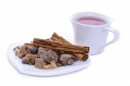 Cup of tea and saucer with cinnamon and candy sugar on a white background photo
