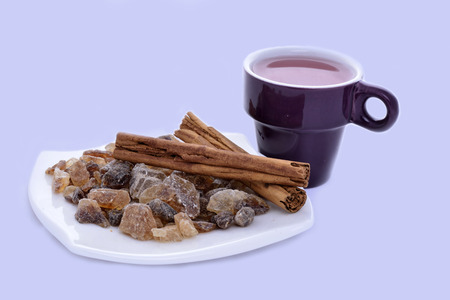 Cup of tea and saucer with cinnamon and candy sugar on a blue background photo