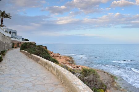 Paved coastal walkway on a summer evening, Cabo Roig, Spain photo