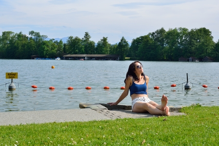 Young woman tanning in front of a lake photo