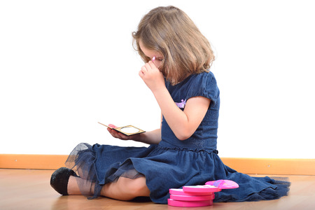 maquillage: Little girl making up while wearing mothers shoes