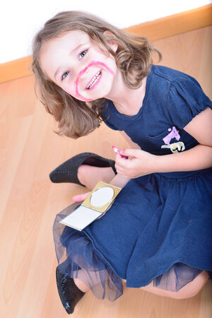 maquillage: Little cute girl using make-up to turn herself into clown