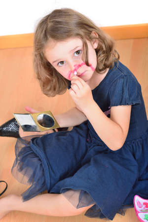 Little cute girl using make-up to turn herself into clown photo
