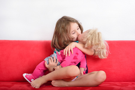 little girl posing: Cute little girl kissing a doll while playing