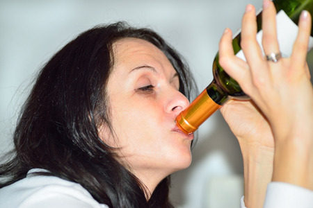 drunk woman: Young drunk woman with a bottle of red wine
