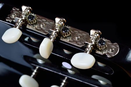 tuning: Head of an acoustic guitar with tuning machine heads and tuning pegs