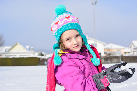 Little cute girl posing in the snow in a sunny winter day photo