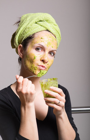 Attractive young woman with spots using a facial avocado mask Archivio Fotografico