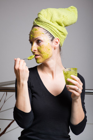 cleanse: Attractive young woman with spots using a facial avocado mask Stock Photo