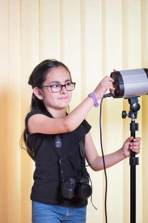 barndoor: Little cute girl learning the lighting technique in a photostudio
