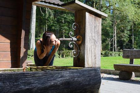 or thirsty: Mujer joven sed bebiendo agua de un viejo pozo de agua de la madera Foto de archivo