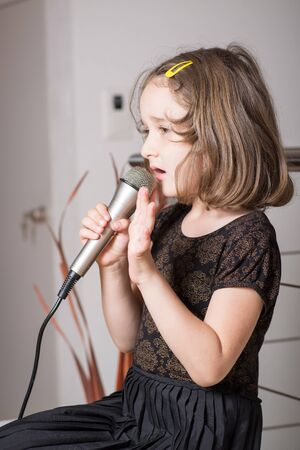 child singing: Little cute girl singing karaoke on microphone at home