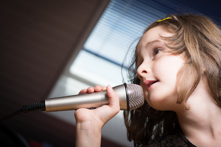 Little cute girl singing karaoke on microphone at home