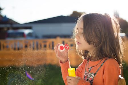 burbujas de jabon: la ni�a, haciendo burbujas de jab�n lindo en el jard�n Foto de archivo