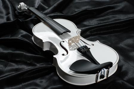 chiave di violino: Closeup of a white violin on a background of  black satin Archivio Fotografico