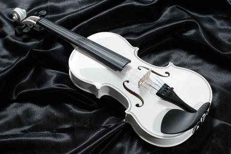 black satin: Closeup of a white violin on a background of  black satin Stock Photo