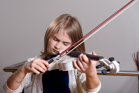 fiddlestick: Cute blonde girl playing violin at home