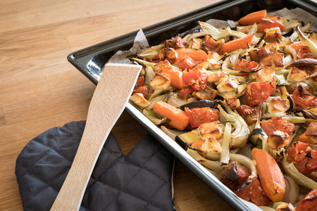 vegetable tin: Roasted vegetables and cheese in a baking tray and a wooden spoon with an oven glove