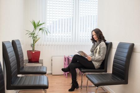 Jonge patiënt het lezen van een tijdschrift in de wachtkamer van artsen