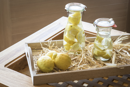 jugs: Jugs of lemon water and lemons on an wooden tray Stock Photo