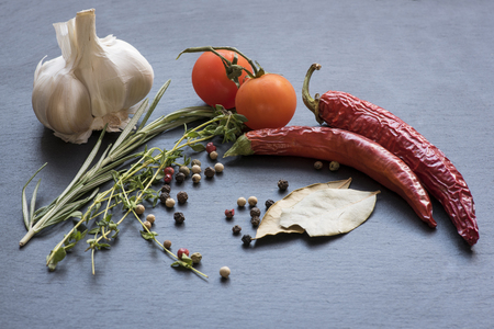 Dry red hot chili peppers, garlic, laurel leafs, tomatoes, seasoning, rosemary and savory on a dark background Stock Photo