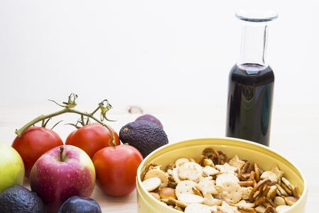Umore d'autunno con mele, prugne, pomodori, avocado, ciotola di metallo con cracker e una bottiglia di vino rosso Archivio Fotografico - 76982254