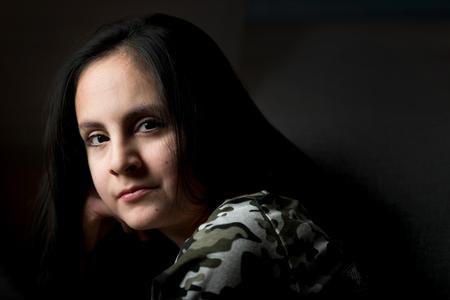 Ragazza sveglia del brunette con capelli lunghi che propongono in scuro Archivio Fotografico - 95437440