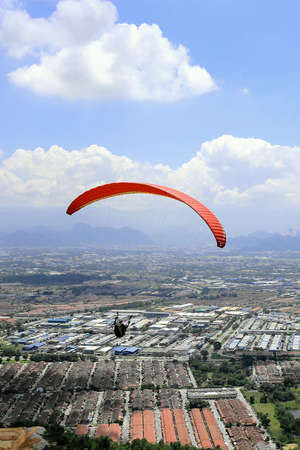 man: A man plays paragliding, glids from kledang mountain, among sky in Ipoh, Malaysia. Stock Photo