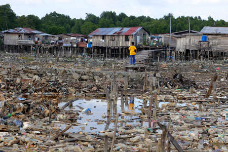 sandakan: A boy walks on a wooden bridge as he goes home among rubbish at Sandakan, Sabah, Malaysia. Stock Photo