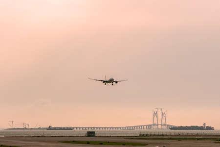 Bridge connecting Zhuhai, Macau and Hong Kong under construction is seen behind the runway of Hong Kong international airport as a plane is landing
