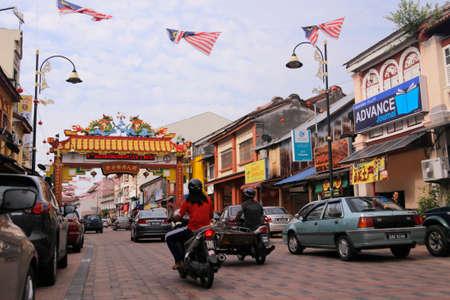 kampung: Vehicles drive along a bricks street passing the gate of Kampung Cina in Kuala Terengganu, Terengganu state. Editorial