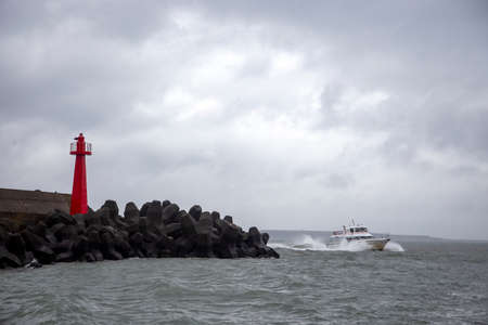 Boat navigates pass a lighthouse at Tamsui Fisherman's Wharf in Taiwan.