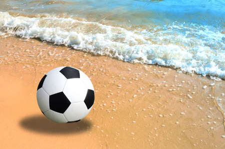 metaphorical: A soccer ball lying in the sand on the beach