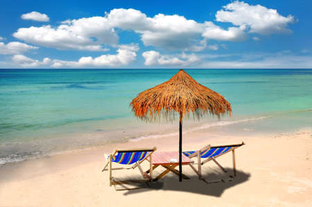 tranquil scene: chairs and umbrella on tropical beach Stock Photo