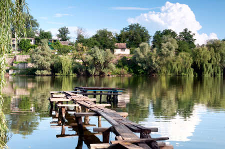 dnieper: View on river with rural buildings and wooden bridge laid up on riverbank. Dnieper, Ukraine