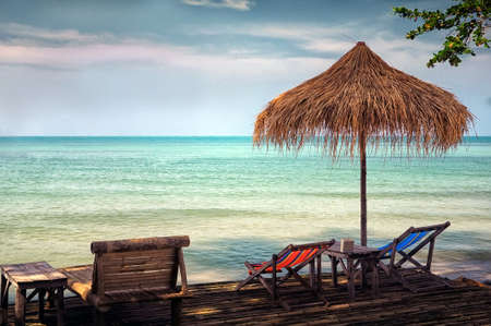 Two chairs and umbrella on stunning tropical beach. photo