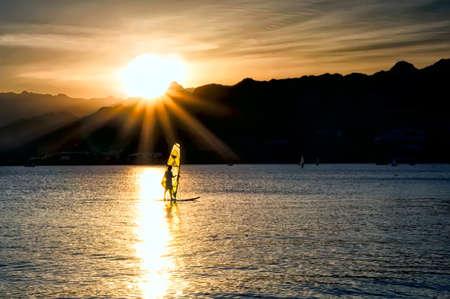 windsurf: Windsurfer vela en el mar al atardecer.
