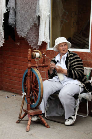 Sergiev Posad, Russia, June 21, 2011: a woman spinning wool with an old-fashioned and traditional Russian spinning wheel