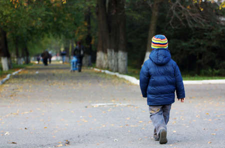 Jongetje loopt weg in de herfst park Stockfoto