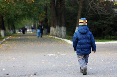 away: Little boy walking away in the autumn park