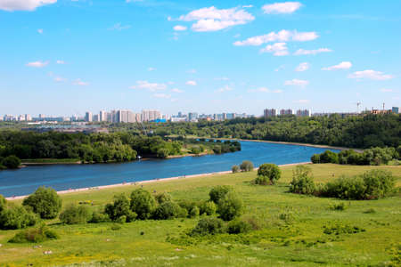 The Moscow river with the green grass in the front and skyscrapers in the background Stock Photo
