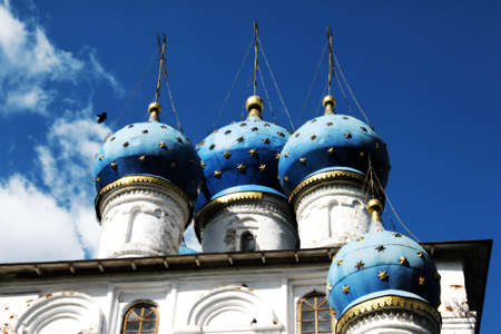 Blue cupola with golden crosses on top as against the blue sky