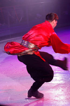 An ice-skater dressed in a Russian costume performing for a show