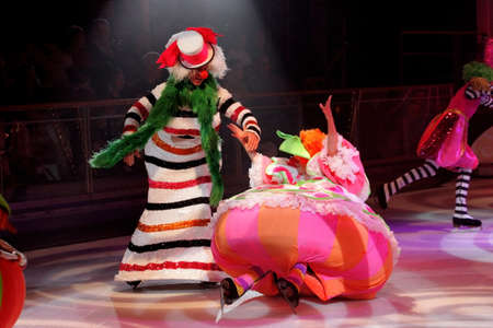 A clown helping another clown to stand up on the ice-skating rink Editorial