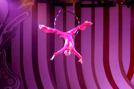 A young girl performing an acrobatic act with a hoop in the air