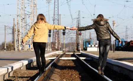 personas ayudando: J�venes amigas tomados de la mano a trav�s de la distancia de los rieles Foto de archivo