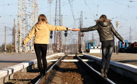Young female friends holding hands through the distance of the rails