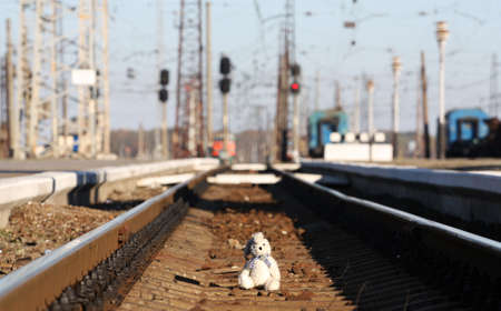 A small rabbit toy left alone in the centre of the railway