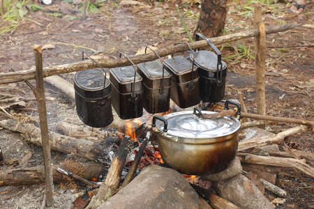 cooker food in pot on fire at camping place photo